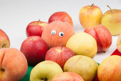 Many real  fruits and peach with eyes. On the light background is several fruits. On the middle of the image is one red color peach with black eyes and is Royalty Free Stock Image