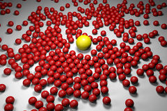 Many red balls among which the yellow one stands out Stock Photo