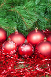 Many red Christmas balls, tinsel and Xmas tree Stock Photos
