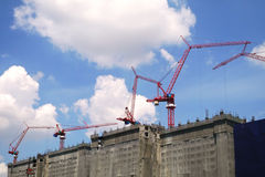 Many red cranes at tall buildings under construction Royalty Free Stock Photography