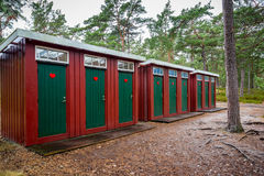 Many red and green wooden outhouse toilets in a row in a forest park. Stock Photography
