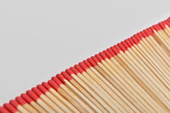 Many red head matches placed straight in line on white backgroun Stock Images
