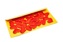 Many red hearts on a yellow envelope. Valentine`s Day and March 8 concept stock images