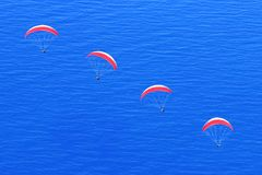 Many red parachutes in the sky above the blue sea. Image in the style of minimalism. Travel concept stock images