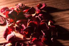 Many red rose petals on wooden background under beam of light with shadows Royalty Free Stock Photos
