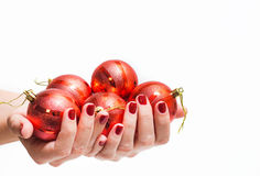 Many red round christmas balls in female hands. Isolated on white background. Close up of young woman hands with beautiful professional red manicure. Christmas royalty free stock photography
