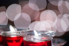 Many Red Wax Candle in Glass with beautiful bokeh on the background. Close-up. Candle light in a straight glass jar Stock Images