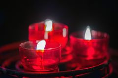Many Red Wax Candle in Glass. Close-up. Candle light in a straight glass jar. Many Red Wax Candle in Glass. Close-up. Candle light in a straight glass jar Royalty Free Stock Photo