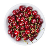 Many red wet cherry fruits in round plate. Many red wet cherry fruits (berries) in round plate, isolated on white Royalty Free Stock Photos
