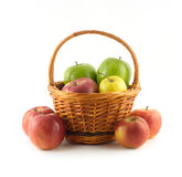 Many ripe color apples in brown wicker basket and near it isolated closeup Stock Images