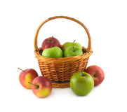 Many ripe color apples in brown wicker basket and near it isolated Royalty Free Stock Photo