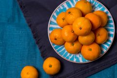 Many ripe delicious juicy Mandarin lie in a bright white with a blue plate patterns on fabric cloth kitchen towel on a dark blue b stock photo