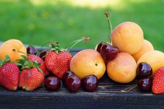 Many ripe, juicy fruits and berries lie on a dark wooden board in nature, summer still life.  stock photo