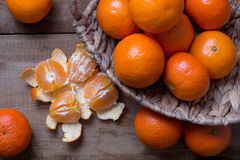 Many ripe mandarins in a basket. One peeled and divided into lobules. Several pcs lie on a wooden table. top view stock photography