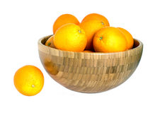 Many ripe oranges in big wooden bowl isolated on white Royalty Free Stock Photos