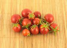 Many ripe tomatoes on sandy brown straw mat Royalty Free Stock Images