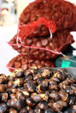 Many roast chestnuts on sale in the market stall Stock Image