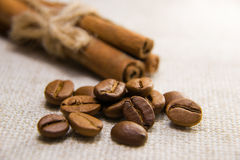 Many of roasted coffee beans and cinnamon on the tablecloth Stock Photo