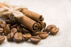 Many of roasted coffee beans and cinnamon on the tablecloth Stock Image