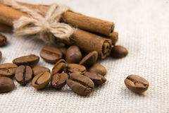 Many of roasted coffee beans and cinnamon on the tablecloth Royalty Free Stock Images