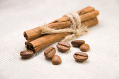 Many of roasted coffee beans and cinnamon on the tablecloth Stock Photos