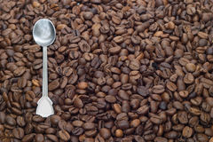 Many roasted coffee beans with silver spoon as bac. Many roasted coffee beans and silver spoon as background close-up Stock Photos
