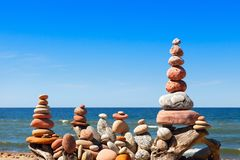 Many of the Rock zen pyramid of white and pink pebbles on a background of blue sky and sea stock image