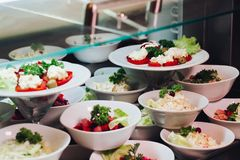 Many round plates with tasty vegetables dish of salads in restaurant. View of many round plates with tasty vegetables dish of salads with tomato, onion stock image