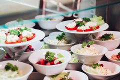 Many round plates with tasty vegetables dish of salads in restaurant. View of many round plates with tasty vegetables dish of salads with tomato, onion stock photography