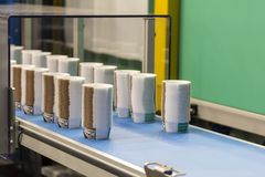 Many row of paper cup on automatic conveyor belt during manufacturing process in factory.  royalty free stock image