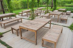 Many row of wooden chair and table setting on beautiful outdoor garden. Many row of wooden chair and table setting on beautiful outdoor garden surrounded with Royalty Free Stock Images