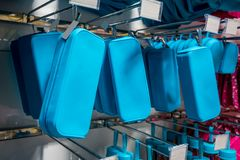 Many rows of blue pencil boxes hanging on metal rack in store. stock images