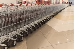 Many rows of red shopping carts outside by store with closeup by parking lot. Inside a large supermarket. Modern and stylish shopping Mall. Grocery store Royalty Free Stock Images