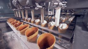 Many rows of wafer cones are getting consequently filled with white creamy substance. 4K stock footage