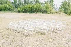Many rows of white wooden chairs for wedding ceremony in nature. Many rows of white wooden chairs for a wedding ceremony in nature Stock Photography