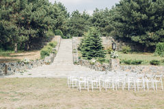 Many rows of white wooden chairs for wedding ceremony in nature. Many rows of white wooden chairs for a wedding ceremony in nature Stock Photo