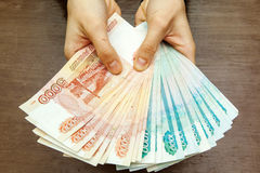 Many rubles banknotes in human hands. Many rubles bills in human hands stock photography