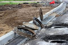 Many rusty round hatches and a rainwater grid on the side of the city road. repair and expansion of the road at the exit of the ci. Ty. Gatchina, Leningrad stock image