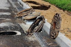 Many rusty round hatches and a rainwater grid on the side of the city road. repair and expansion of the road at the exit of the ci. Ty. Gatchina, Leningrad royalty free stock photo