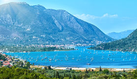 Many sailing vessels in bay (Nydri, Lefkada, Greece). Many sailing vessels in bay. Hazy summer Lefkada coast panorama (Nydri, Greece, Ionian Sea Royalty Free Stock Photos