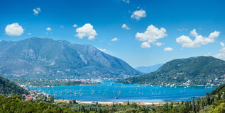 Many sailing vessels in bay Nydri, Lefkada, Greece. Many sailing vessels in bay. Hazy summer Lefkada coast panorama Nydri, Greece, Ionian Sea Royalty Free Stock Photos