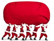 Santa claus carrying big and heavy gift red sack royalty free stock image