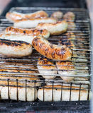 Many sausage cooking in grilled barbecue Stock Images
