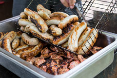 Many sausage cooking in grilled barbecue Stock Image
