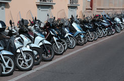 Many scooters and motorcycles parked along the busy street Royalty Free Stock Photography