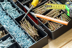 Many screws in plastic organizer box, work tools. Many screws in plastic organizer box top view Stock Photo