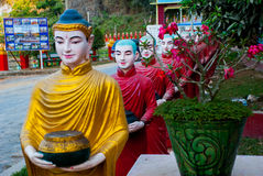 Many sculptures of monks at the entrance to the sacred cave that face each other. Hpa-An, Myanmar. Burma Royalty Free Stock Photo