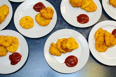 Many servings of potato pancakes with ketchup on plates Stock Image