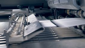Paper sheets getting on a typography conveyor, close up. Many sheets on a typography line stock video footage