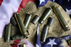 Bullet and usa flag in the sand war. Many shell casings from bullets of different caliber in the background chaos concept in the world Royalty Free Stock Photography